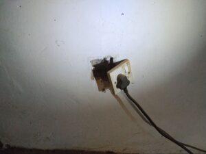 Steckdose, welche aus der Wand hängt.