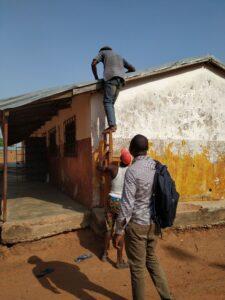 Konstruktion aus zwei Stühlen, welche zum Besteigen des Dachs des ICT-Labs verwendet wurde. Person klettert gerade auf das Dach.